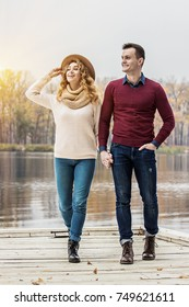 Enjoying carefree walk. Full-length of beautiful young couple walking outdoors. Gorgeous woman and handsome man looking away and smiling while having fun outdoors.