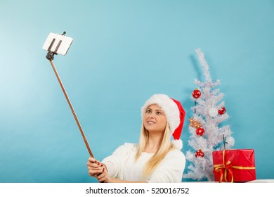 Enjoying christmas gifts. Woman in santa hat taking picture of herself using selfie stick. Indoor shot on blue background