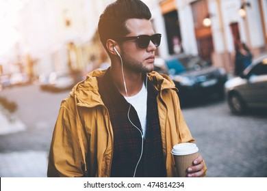 Enjoying city life. Handsome young man in headphones carrying coffee cup while walking along the city street