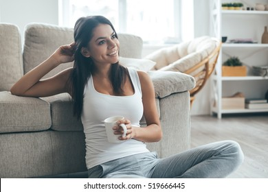 Enjoying coffee at home. Attractive young smiling woman sitting on the carpet at home and holding coffee cup