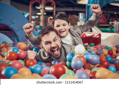 Enjoying dad and son in pool with balls. Family rest, leisure. Spending holiday together with family. Entertainment center, mall, amusement park.