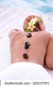 Enjoying day spa, cute female with frangipani flowers in hair lying down on massage table on the beach, black hot stones therapy, zen balance concept