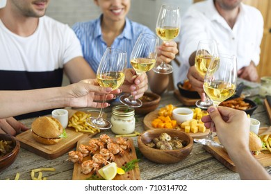 Enjoying dinner with friends. Group of people having dinner together while sitting at the rustic wooden table