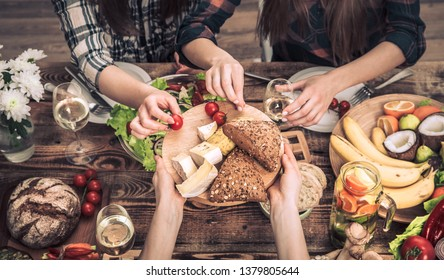 Enjoying dinner with my friends. Top view of a group of people dining together, sitting at a rustic wooden table, the concept of celebration and healthy home-cooked food