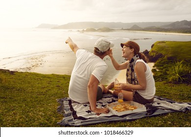 Enjoying dinner outdoors. Cheerful young people spending nice time together while sitting on the coastline and eating pizza