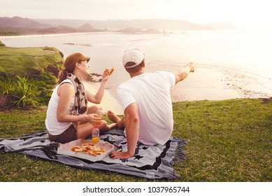 Enjoying dinner outdoors. Cheerful young people spending nice time together while sitting on the coastline sea and eating pizza