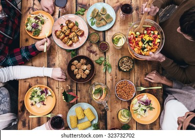 Enjoying dinner together. Top view of four people having dinner together while sitting at the rustic wooden table