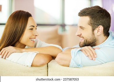 Enjoying each other. Beautiful young loving couple sitting together on the couch and looking at each other with smile