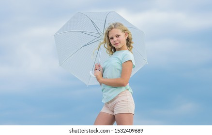 Enjoying ease. Carefree child outdoors. Girl with umbrella cloudy sky background. Freedom and freshness. Weather forecast. Ready for any weather. Weather changing. Fresh air. Happy childrens day.