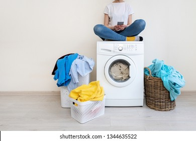 Enjoying of easy laundry process. Attractive woman sitting with smartphone in hands on top of washing machine inside bright apartment interior
