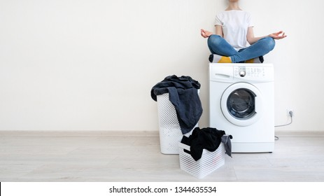 Enjoying of easy laundry process. Attractive woman in denim jeans wear sitting inside apartment with light interior on top of white washing machine in meditation pose