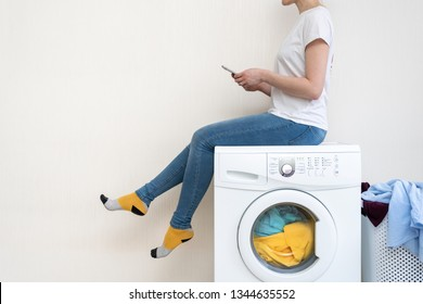 Enjoying of easy laundry process. Profile side view of lady sitting on top of white washing machine and looking at smartphone app inside bright light flat interior
