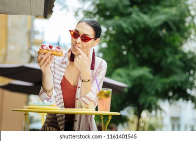 Enjoying eclairs. Calm young woman looking attentively at the dessert in her hand and licking her finger while sitting in a cafe