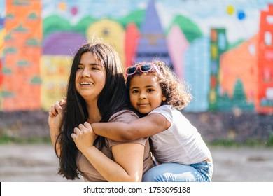 Freuen Sie sich auf die ecuadorianische Mutter, die eine junge, dunkelhäutige Tochter auf den Schultern trägt, während sie auf dem Spielplatz zusammen spaziert. Unscharfe Kinder zeichnen auf Hintergrund.