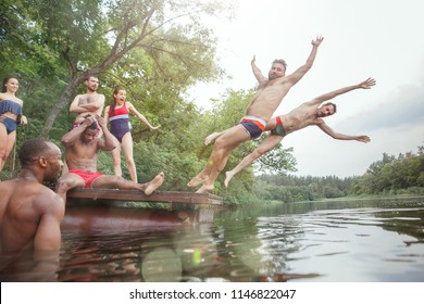 Enjoying forest party with friends. Group of beautiful happy young men and girls swimming at the river together. Summer, party, adventure, youth, frienship concept
