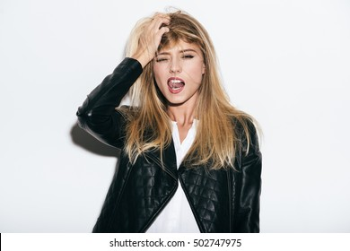 Enjoying freedom. Funky young woman in leather coat holding hand in hair and sticking out tongue while standing against white background