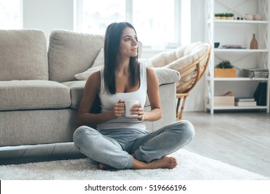 Enjoying fresh coffee at home. Attractive young woman sitting on the carpet at home and holding coffee cup