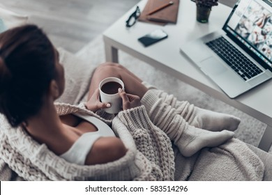 Enjoying fresh coffee. Top view of beautiful young woman holding cup while relaxing on couch at home