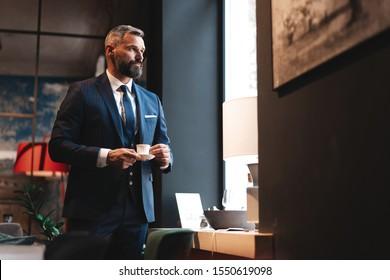 Genießen Sie den frischen Kaffee während der Arbeit. Vertrauter Mann mit kluger Freizeitbekleidung, der eine Kaffeetasse an seinem Arbeitsplatz hält