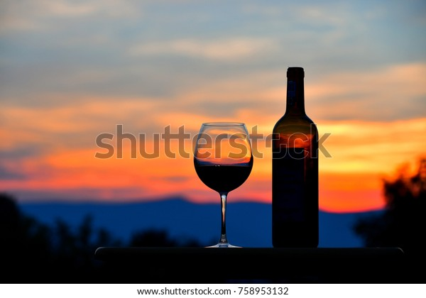 Enjoying a glass of red wine while watching the sunset over the mountains in the Shenandoah Valley of Virginia while on a romantic summer vacation