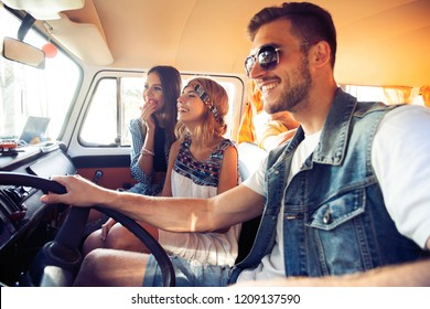 Enjoying great roadtrip with friends. Group of cheerful young people having fun while sitting inside of minivan