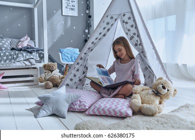 Enjoying great story. Cute little girl reading book while sitting on the floor in tent