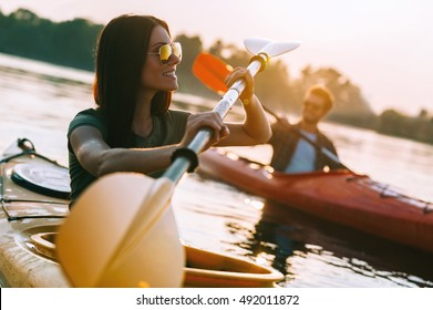Enjoying great time on river.Beautiful young couple kayaking on river together and smiling to you