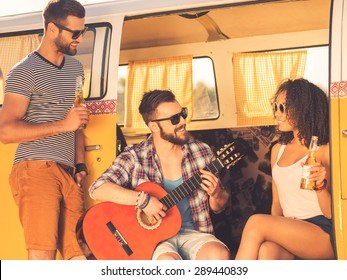 Enjoying great time together. Cheerful young beard man sitting in retro minivan and playing guitar while two his friends looking at him and smiling