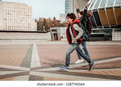 Enjoying happy childhood. Joyful children running through the city square
