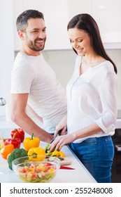Enjoying healthy lifestyle. Beautiful young and cheerful woman cutting vegetable in the kitchen while her husband standing close to her and smiling