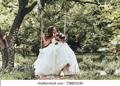 Enjoying her day. Attractive young woman in wedding and sports shoes looking away and smiling while sitting on the swing outdoors