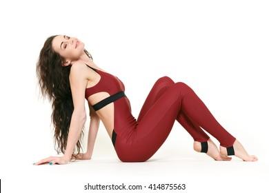 Enjoying her life. Gorgeous happy brunette gymnast woman sitting gracefully smiling with her eyes closed joyfully