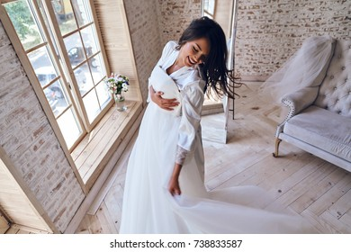 Enjoying her special day. Top view of attractive young woman in silk bathrobe trying on her wedding dress and smiling while standing near window