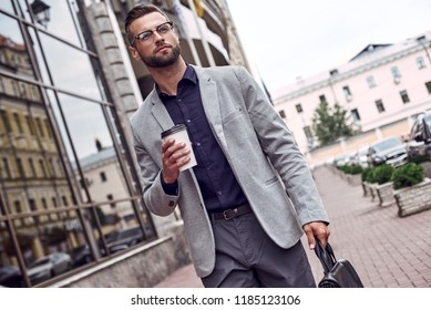 Enjoying his coffee break. Handsome young man holding disposable cup and briefcase while walking outdoors pensive