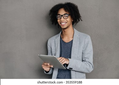 Enjoying his digital tablet. Cheerful young African man holding digital tablet and smiling while standing against grey background