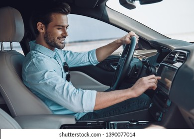 Enjoying his drive. Handsome young man in smart casual wear smiling while driving a status car