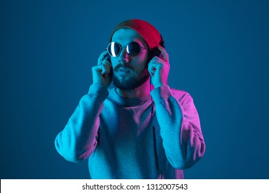 Enjoying his favorite music. Happy young stylish man in hat and sunglasses with headphones listening and smiling while standing against blue neon background