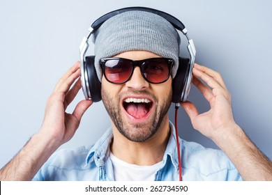 Enjoying his favorite song. Happy young stylish man in headphones expressing positivity and looking at camera while standing against grey background