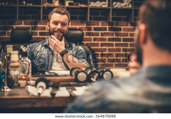 Enjoying his perfect beard. Handsome young bearded man looking at his reflection in the mirror and keeping hand on chin while sitting in chair at barbershop