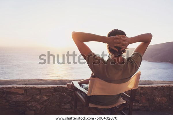 Enjoying life. Back side of young man looking at the sea, vacations lifestyle concept