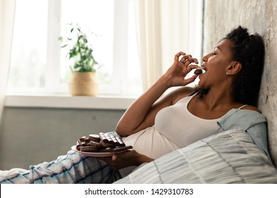 Enjoying life. Beautiful happy pregnant woman laying in her bed eating chocolate candies.