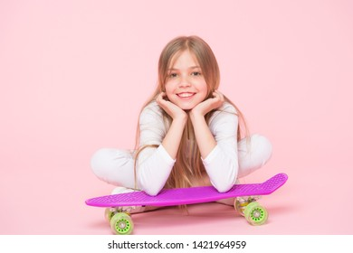 Enjoying life in the extreme speed. Happy small extreme athlete relaxing at violet penny board on pink background. Cute little child taking pleasure in extreme sport. Getting ready for some extreme.