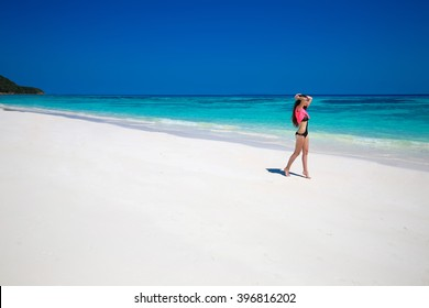 Enjoying life. Healthy woman walking on exotic sea. Fit brunette girl, blue sky on tropical beach. outdoor summer portrait. Bliss freedom concept. Travel.