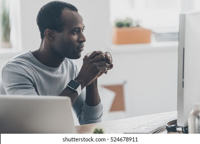 Enjoying morning coffee. Thoughtful young African man holding a cup and looking at the computer monitor while sitting at the desk in creative office