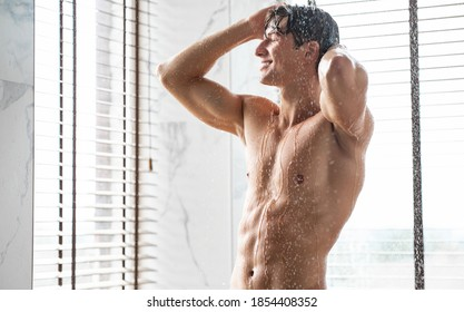 Enjoying The Morning. Portrait Of Handsome Muscular Man Taking A Shower Washing Head Standing Under Falling Hot Water In Modern Bathroom At Home. Male Bodycare Beauty Routine And Everyday Hygiene
