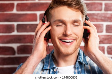 Enjoying music. Handsome young man listening to the MP3 Player and keeping eyes closed while standing against brick wall