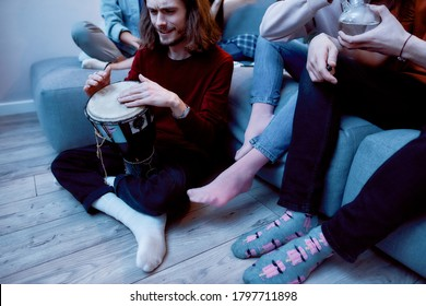 Enjoying music. Happy young man playing bongo or ethnic drum while sitting on the floor and relaxing with friends at home. Young people sitting on the sofa and resting together. Home party.