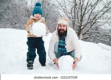 Enjoying nature wintertime. Father and son making snowball on winter white background. Happy family plaing with a snowball on a snowy winter walk