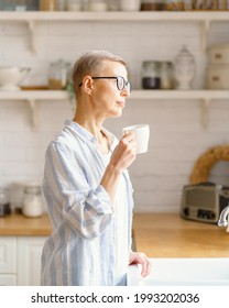Enjoying new day. Thoughtful beautiful mature woman holding cup of coffee or tea, pure water, looking in window and thinking or dreaming. spending free time in Sunday morning at home, vertical