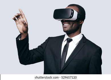 Enjoying new experience. Handsome young African man in VR headset gesturing and smiling while standing against grey background
